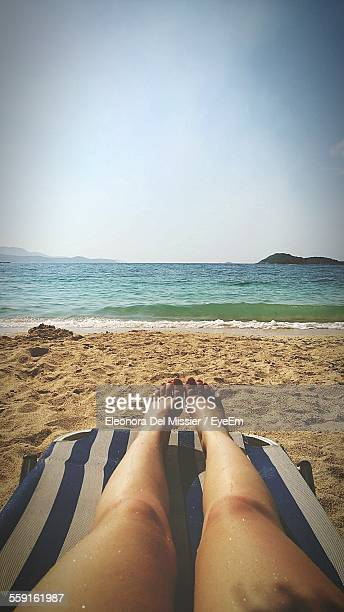 Low Section Of Woman On Lounge Chair At Beach By Sea Against Clear Sky