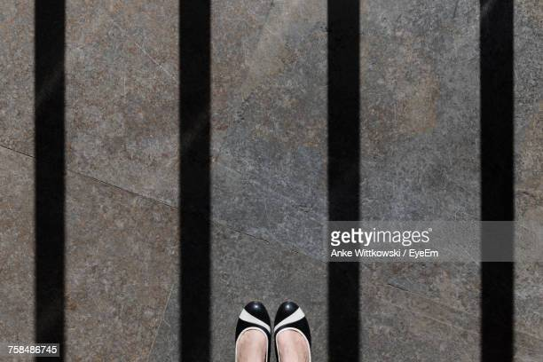 low section of woman on marble flooring with shadow of prisoner bars - woman prison stock-fotos und bilder