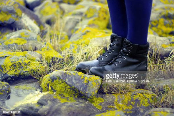 low section of woman on stones - black boot stock pictures, royalty-free photos & images