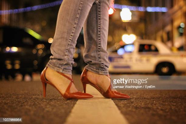 low section of woman on street at night - high heels stock pictures, royalty-free photos & images