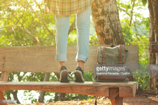 Low Section Of Woman On Tiptoes Standing On Park Bench