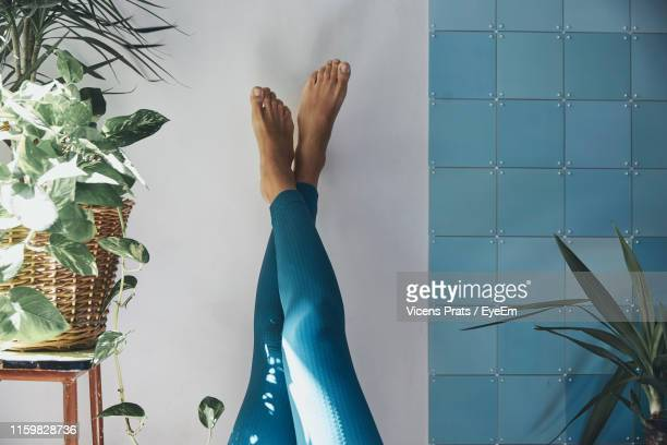 low section of woman on wall at home - leggings stock pictures, royalty-free photos & images