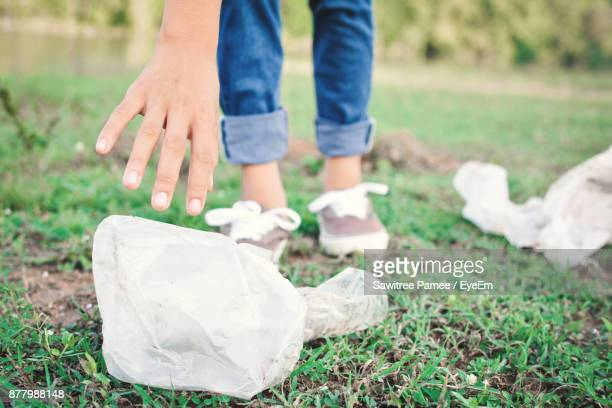 Low Section Of Woman Picking Garbage On Field At Park