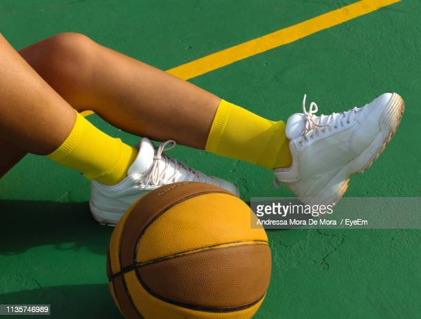 low section of woman playing basketball on court - yellow shoe stock pictures, royalty-free photos & images