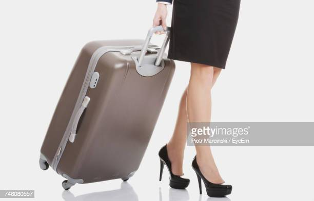 Low Section Of Woman Pulling Luggage Over White Background