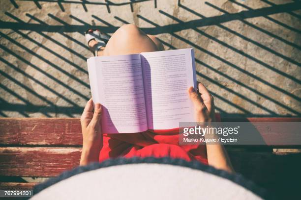 low section of woman reading book - reading stock photos and pictures