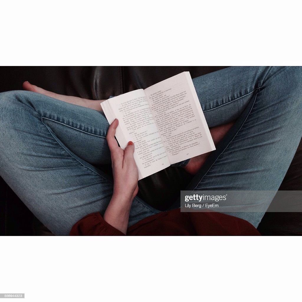 Low Section Of Woman Reading Books At Home : Stock Photo