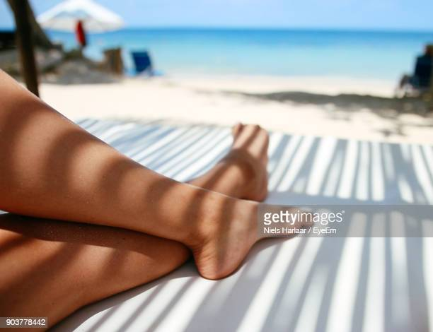 Low Section Of Woman Relaxing Against Sea At Beach