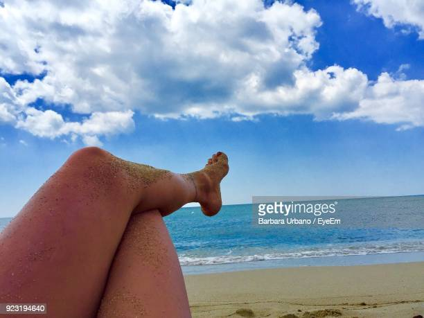 Low Section Of Woman Relaxing At Beach Against Sky