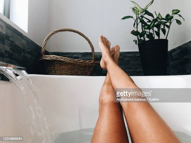 low section of woman relaxing at home in the bathtub - human foot stock pictures, royalty-free photos & images