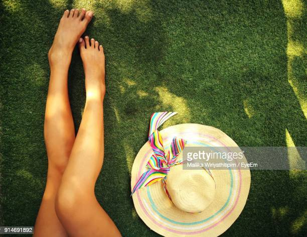 Low Section Of Woman Relaxing By Hat On Grassy Field