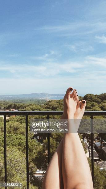 low section of woman relaxing by railing - legs crossed at ankle stock pictures, royalty-free photos & images