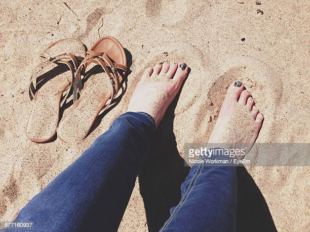 Low Section Of Woman Relaxing By Slipper On Sandy Beach