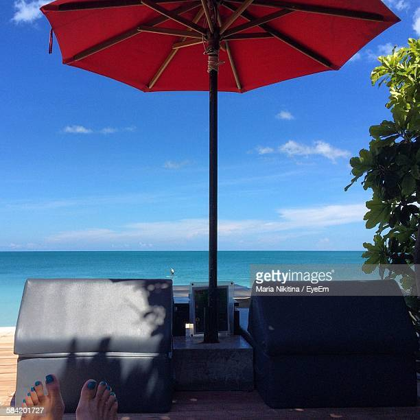 low section of woman relaxing lounge chair at beach - nikitina stock pictures, royalty-free photos & images