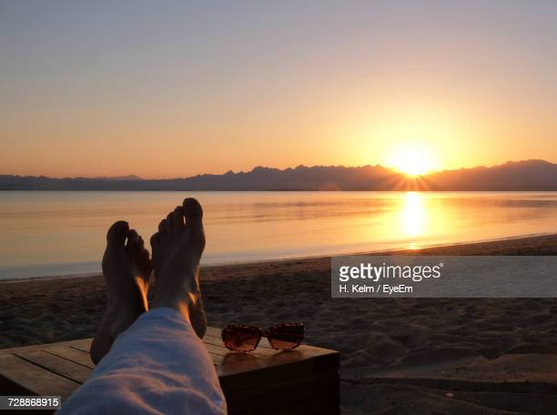 Low Section Of Woman Relaxing On Beach During Sunset