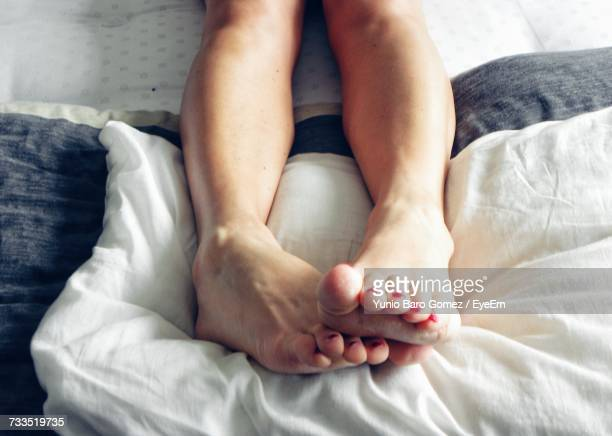 Low Section Of Woman Relaxing On Bed