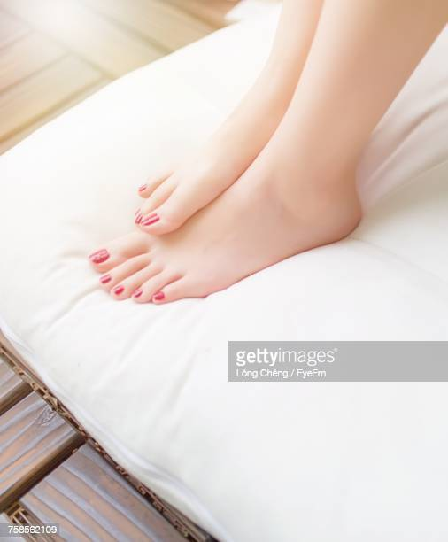 low section of woman relaxing on bed - pretty asian feet stock photos and pictures