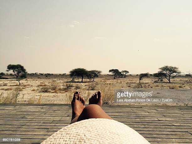 Low Section Of Woman Relaxing On Boardwalk At Etosha National Park