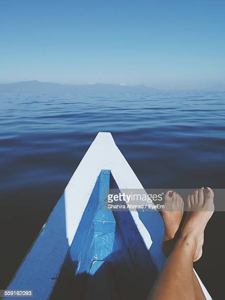 low section of woman relaxing on boat in sea - legs crossed at ankle stock pictures, royalty-free photos & images