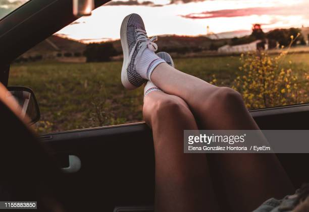 low section of woman relaxing on car window against sky during sunset - legs crossed at ankle stock pictures, royalty-free photos & images