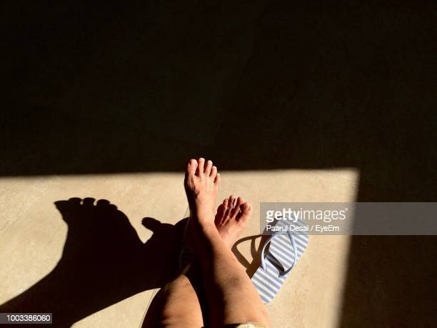 Low Section Of Woman Relaxing On Floor During Sunny Day