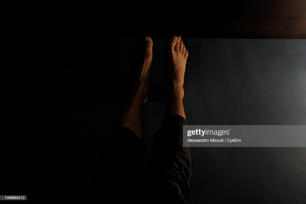 Low Section Of Woman Relaxing On Flooring In Darkroom At Home : Stock Photo