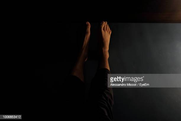 low section of woman relaxing on flooring in darkroom at home - alessandro miccoli fotografías e imágenes de stock