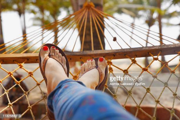 low section of woman relaxing on hammock at beach - legs crossed at ankle stock pictures, royalty-free photos & images