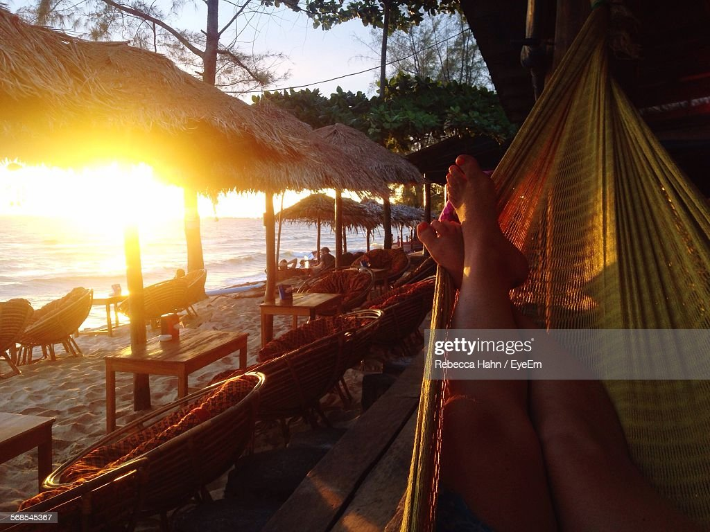 Low Section Of Woman Relaxing On Hammock By Parasols At Beach During Sunset : Stock Photo