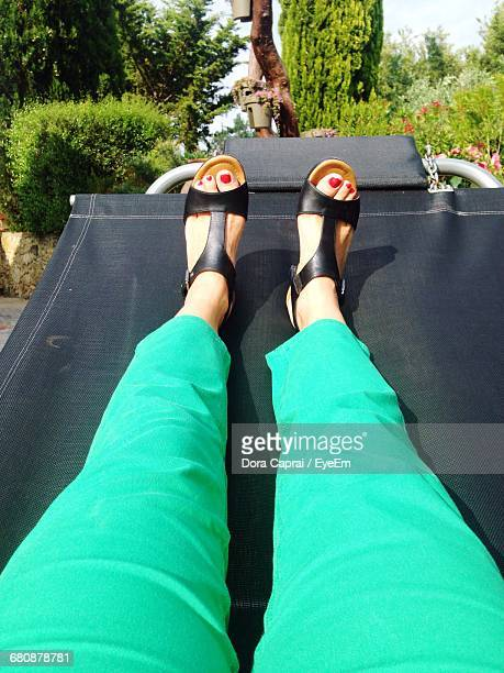 Low Section Of Woman Relaxing On Outdoor Chair