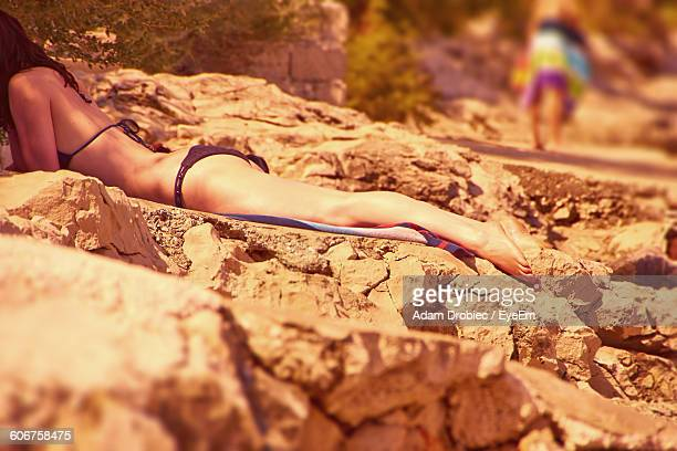 Low Section Of Woman Relaxing On Rock Formation At Shore