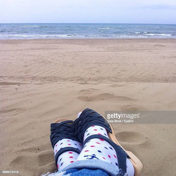 Low Section Of Woman Relaxing On Sand At Beach Against Sky