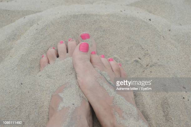 Low Section Of Woman Relaxing On Sand At Beach