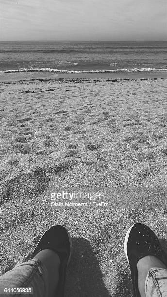 Low Section Of Woman Relaxing On Sandy Beach