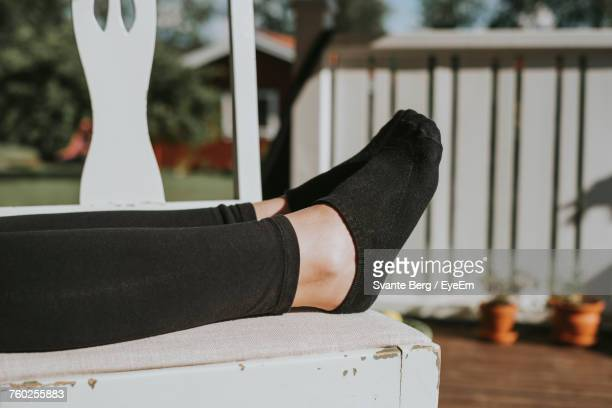 Low Section Of Woman Relaxing On Wooden Table At Yard