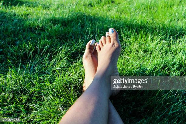 Low Section Of Woman Relaxing With Legs Crossed At Ankle On Grassy Field