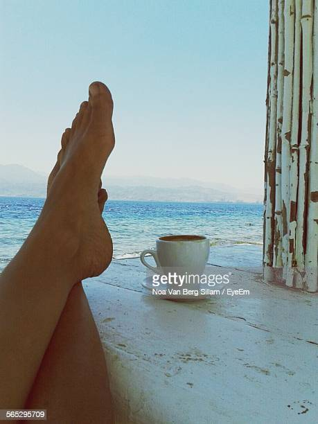 Low Section Of Woman Relaxing With Legs Crossed On Table At Beach