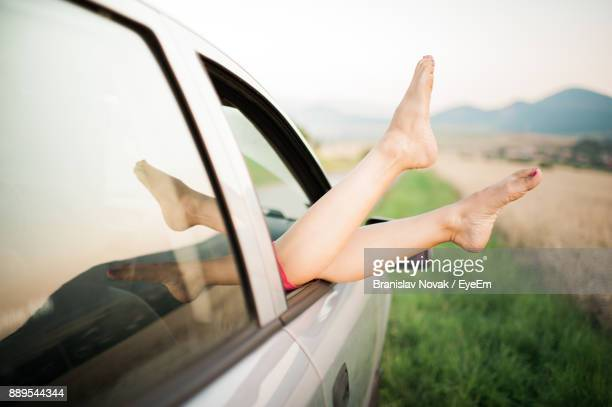 Low Section Of Woman Resting In Car Against Sky