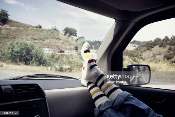 low section of woman resting in car by hills - legs crossed at ankle stock pictures, royalty-free photos & images