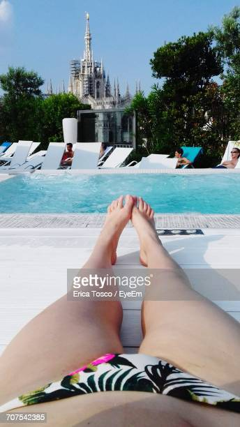 Low Section Of Woman Resting On Lounge Chair At Poolside Against Duomo Di Milano