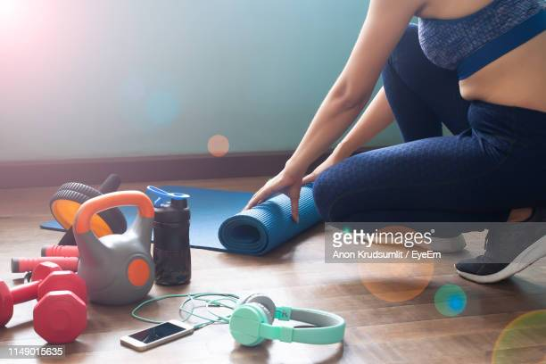 low section of woman rolling exercise mat on hardwood floor - home workout stock pictures, royalty-free photos & images