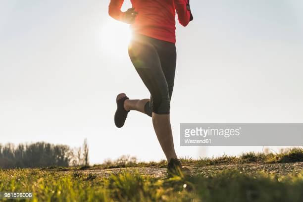 low section of woman running on rural path - joggen stock-fotos und bilder