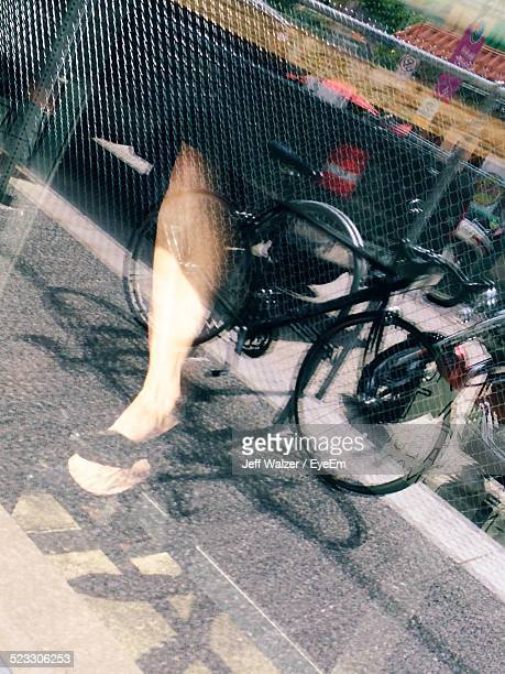 Low Section Of Woman Seen Through Glass Window With Bicycle Reflection