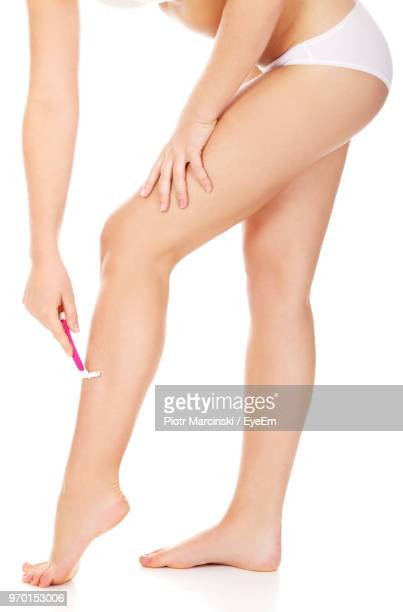 Low Section Of Woman Shaving Leg Against White Background