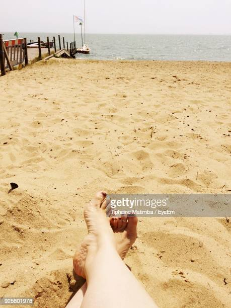 Low Section Of Woman Sitting At Beach Against Sky