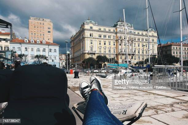 low section of woman sitting at waterfront - rijeka stock pictures, royalty-free photos & images