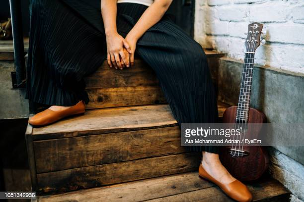 Low Section Of Woman Sitting By Ukulele On Steps
