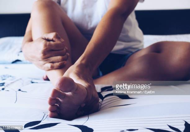 low section of woman sitting on bed at home - feet stock pictures, royalty-free photos & images