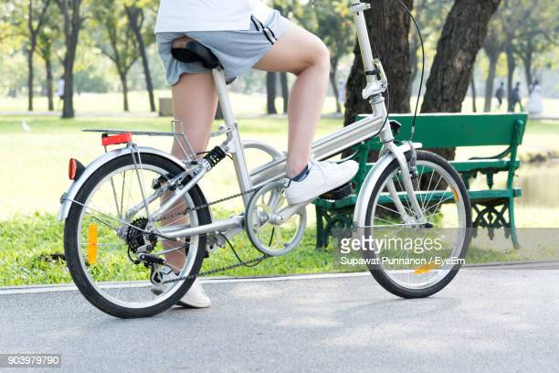low section of woman sitting on bicycle in park - pedal stock pictures, royalty-free photos & images