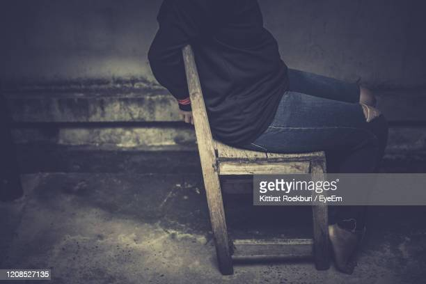 low section of woman sitting on chair in abandoned building - kidnapping stock pictures, royalty-free photos & images